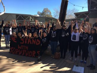 Students at the pop-up protesting, arms raised