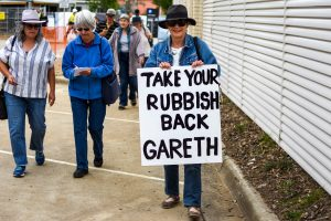 Protester holding sign reading 'Take Back Your Rubbish Gareth'