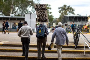 Protester holding a sign reading 'Stop Dumping Your Waste in the Bidgee [sic]'