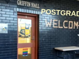 "A picture of the outside of Griffin Hall, with a sign edited to read ""Postgrads welcome"""
