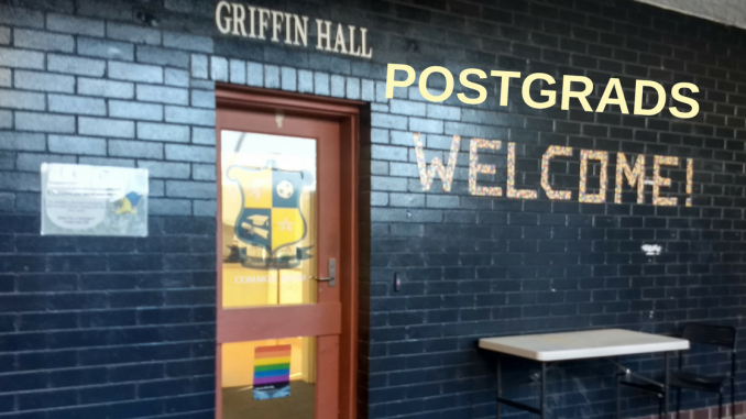 """A picture of the outside of Griffin Hall, with a sign edited to read """"Postgrads welcome"""""""