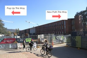 Photo of the construction with signs showing the pop-up one way, and the new path the other way