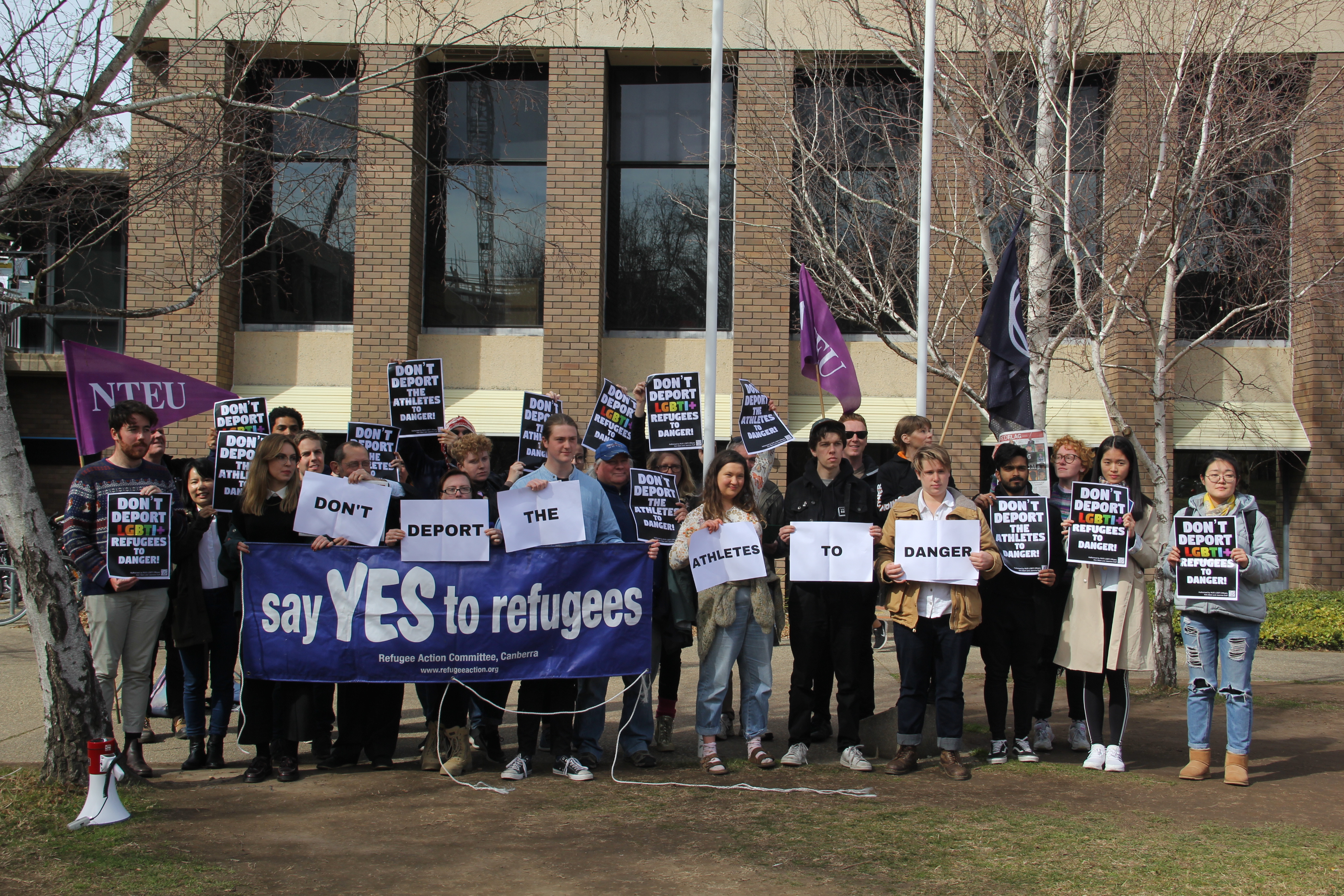 Approximately 20 students with banner 'say YES to refugees'