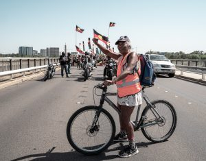 An Indigenous woman stands on a bridge waving the Aboriginal flag