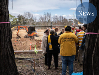 Students and staff in Burgmann merchandise gather near the fence near the construction site